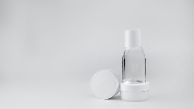 Weiße behälter mit kosmetika (gesichtscreme, handcreme, verschiedenes wasser) auf einem weißen hintergrund, vertikal angeordnet