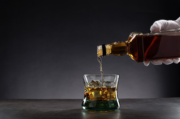 Weiße behandschuhte hand, die whisky in ein glas mit eis auf dunkelheit gießt