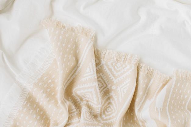 Weiße bettwäsche mit warmem plaid. gemütlicher hintergrund mit kopienraum. skandinavischer stil.