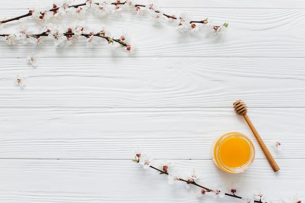 Weiße blüten und honig auf holzuntergrund