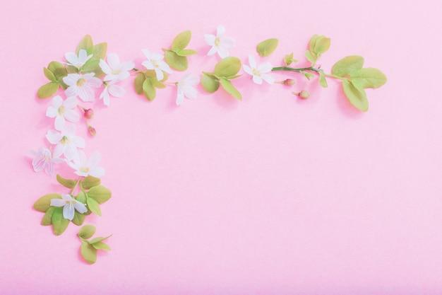 Weiße blumen auf rosa papierhintergrund