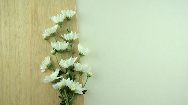 Weiße blumen flach auf holzplatte und grauweißem hintergrund liegend minimaler stil