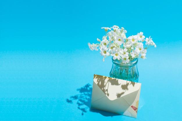 Weiße blumen in einem glas auf blau