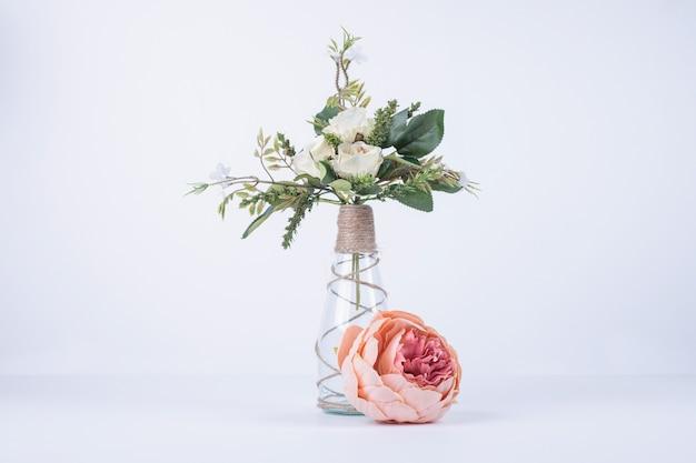 Weiße blumen in glasvase auf weiß mit einzelner rose.