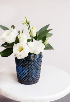 Weiße blumen in klassischem blauem glas. lisianthus. eustoma.