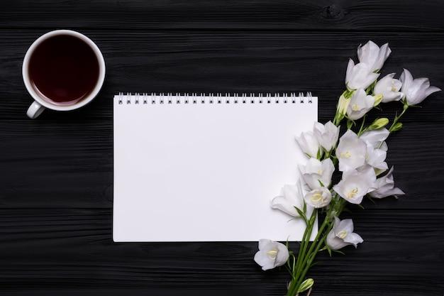 Weiße blumen, kaffee und leeres notizbuch auf einem schwarzen