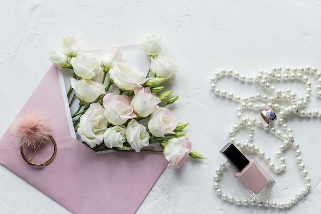 Weiße blumen, perlenkette, parfüm, grußkarte auf weiß. zubehör und blumen. online-shopping oder dating-konzept mit kopierraum.