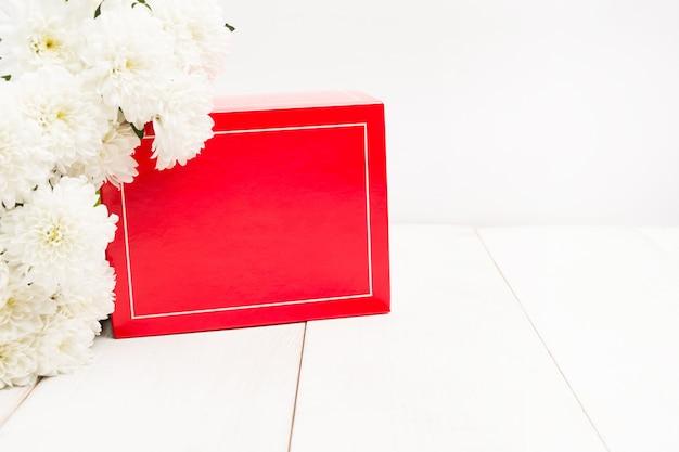 Weiße blumendekoration auf roter geschenkbox