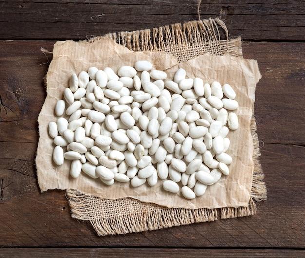 Weiße bohnen auf brauner hölzerner tischoberansicht