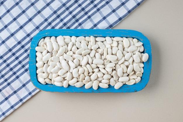Weiße bohnen auf einer quadratischen platte auf dem beton.