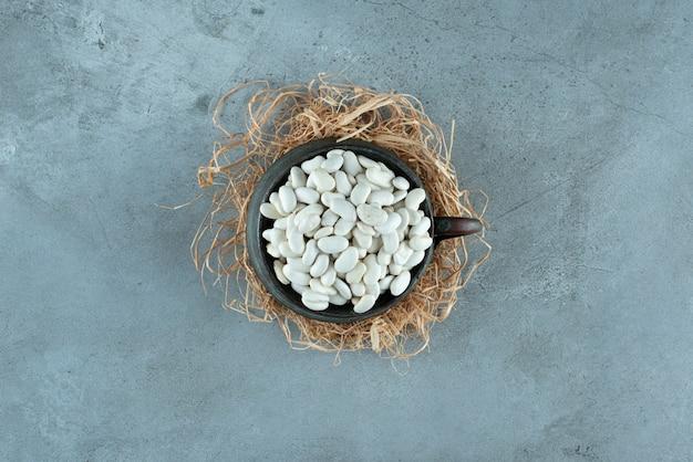 Weiße bohnen in einem schwarzen metallischen topf. foto in hoher qualität