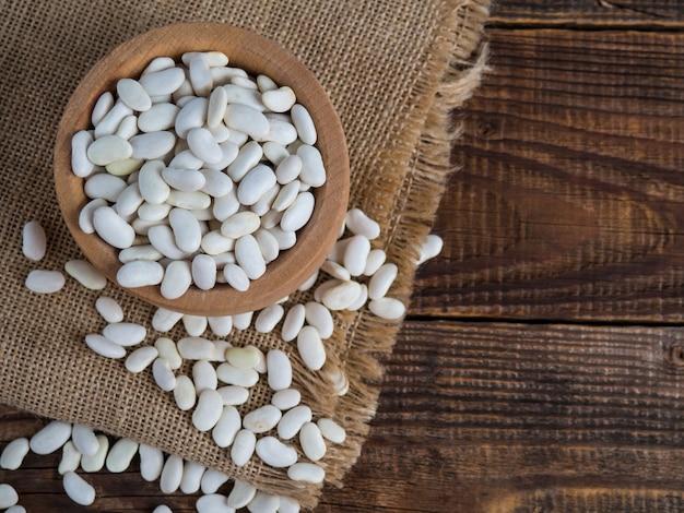 Weiße bohnen in einer holzschale auf einem alten holztisch, hülsenfrüchte, kopierraum