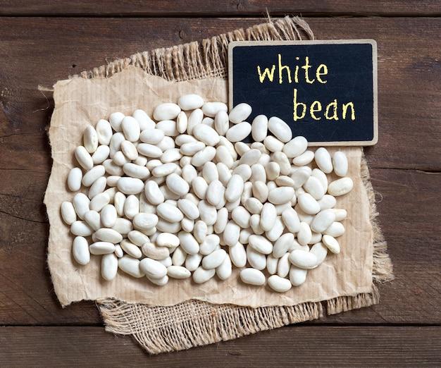 Weiße bohnen mit einer kleinen tafel auf brauner hölzerner tischoberansicht