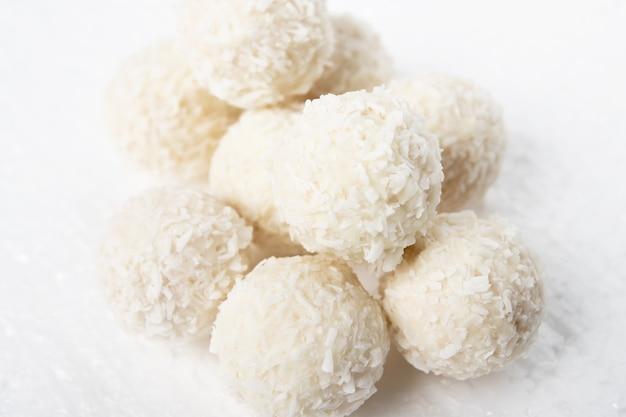 Weiße bonbons mit kokos, nüssen und sahne auf weißem hintergrund