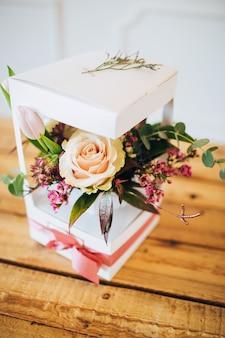 Weiße box mit blumen. schachtel mit pfingstrosenrosen und weißen tulpen. gartenblumen in blumentöpfen. wildblumen.