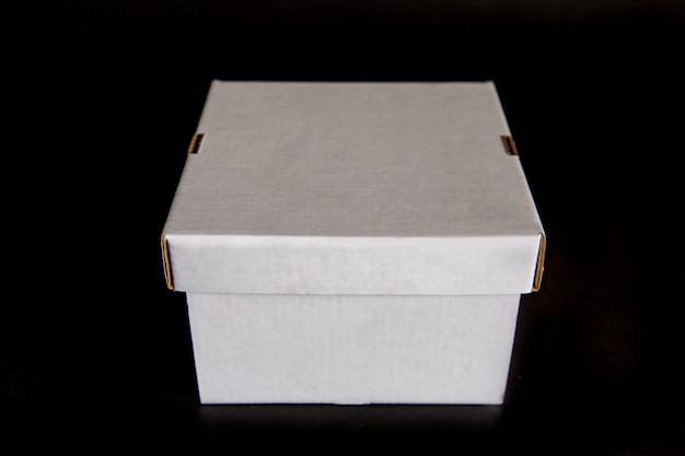 Weiße box mit einem deckel isoliert auf einem schwarzen raum. vorlage für design, layout.