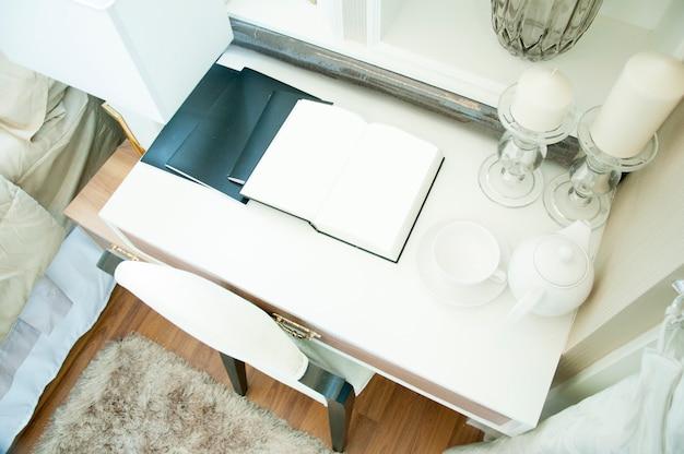 Weiße buchseite offen auf der tabelle im luxusschlafzimmer.