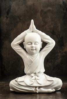 Weiße buddha-skulptur auf dunklem hintergrund. meditation und entspannung