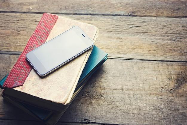 Weiße bücher des smartphones auf dem holztisch
