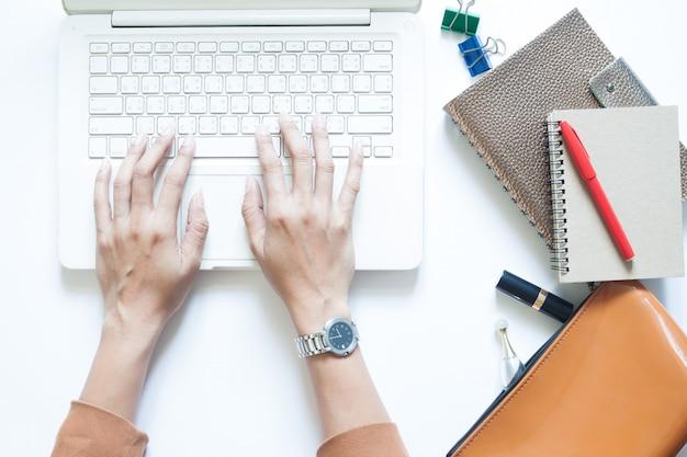 Weiße büro schreibtisch tisch mit geschäftsfrau mit laptop und kaffee trinken