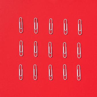 Weiße büroklammern auf rotem pastellhintergrund