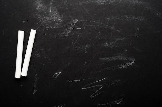 Weiße buntstifte auf einer bemalten schwarzen tafel. schulbehörde, konzeptioneller hintergrund. kopierraum, draufsicht, flache lage.