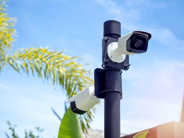 Weiße cctv-kameras auf dem schwarzen pfosten im garten nahe dem gebäude