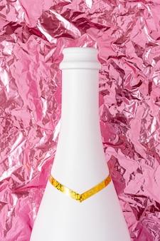Weiße champagnerflasche auf rosa zerknitterter folienoberfläche.