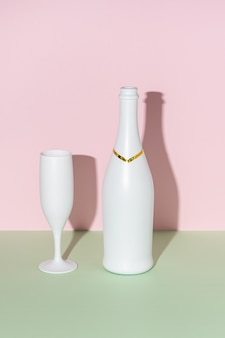 Weiße champagnerflasche und champagnerglas auf hellem hintergrund.
