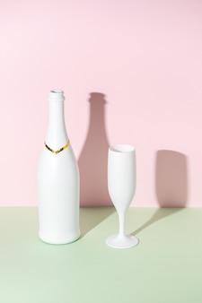 Weiße champagnerflasche und champagnerglas auf heller oberfläche.