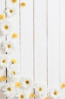 Weiße chrysantheme und gelber huflattich auf weißem hölzernem hintergrund