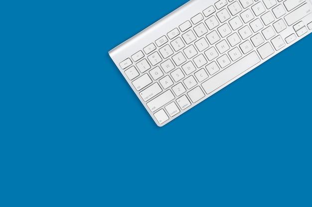Weiße computertastatur auf himmelblauem hintergrund mit kopienraum