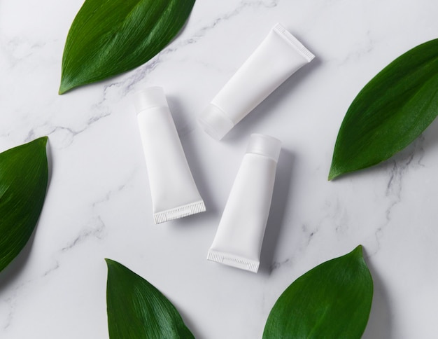 Weiße cremetuben auf einem marmorhintergrund mit grünen blättern