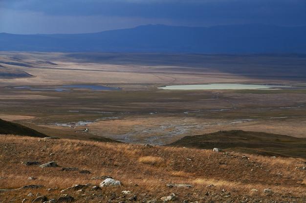 Weiße cumuluswolken kommen von den bergen, herbstlandschaft in der steppe herunter