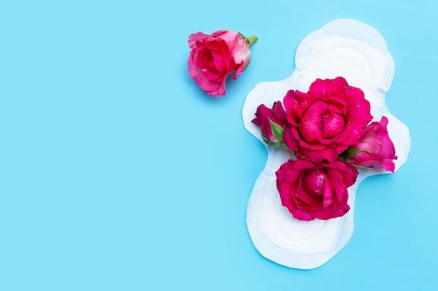 Weiße damenbinde mit roten rosen auf blauer oberfläche