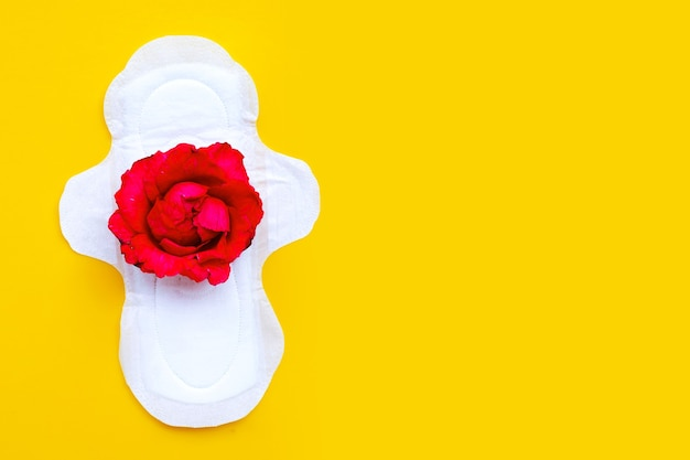 Weiße damenbinde mit roter rose auf gelber oberfläche