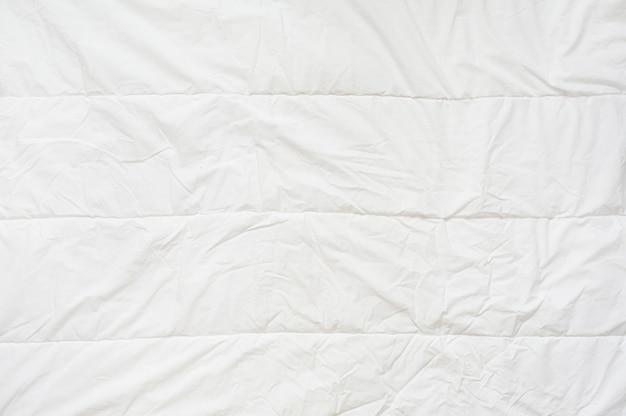 Weiße decke der zerknitterten steppdecke. nahansicht. draufsicht