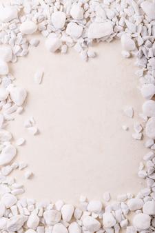 Weiße dekorative felsen und kieselsteine als rahmen über weißem texturhintergrund. kreatives layout der natur. platz für design