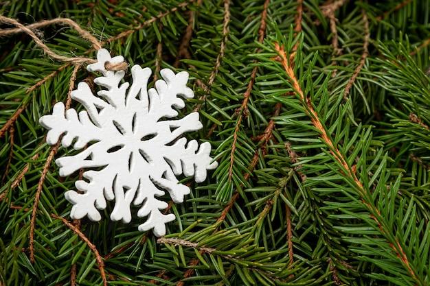 Weiße dekorative schneeflocke auf fichtenzweigen