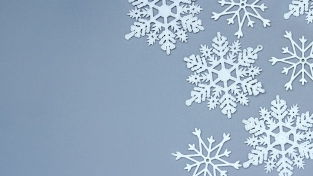 Weiße dekorative schneeflocken auf grauem hintergrund. weihnachten und neujahr, ein ort für text, minimalismus, winterhintergrund