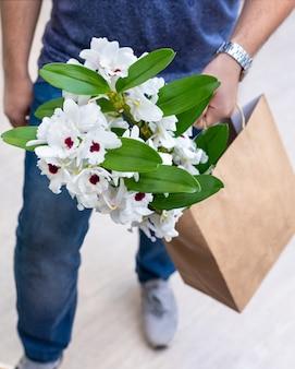Weiße dendrobium nobile orchideenblume in einkaufstasche