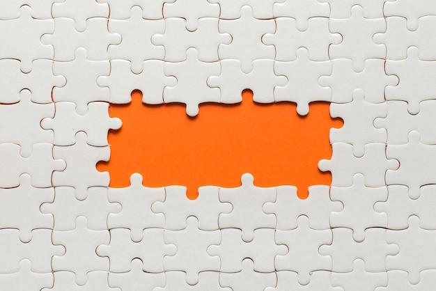 Weiße details des puzzles auf orange und platz für inschrift.
