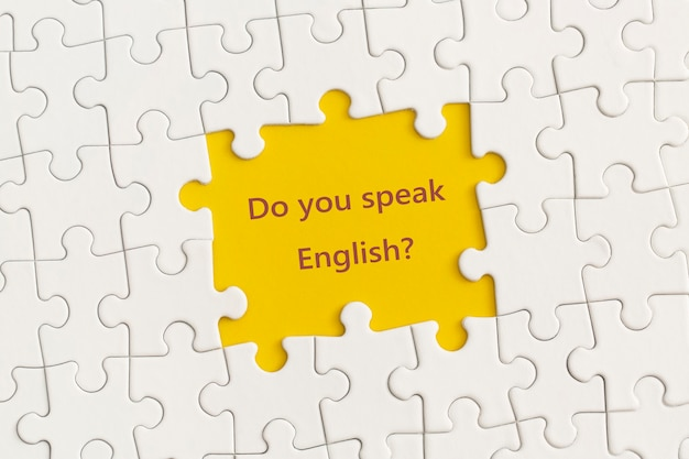 Weiße details des puzzles mit dem text sprechen sie englisch auf gelbem hintergrund?