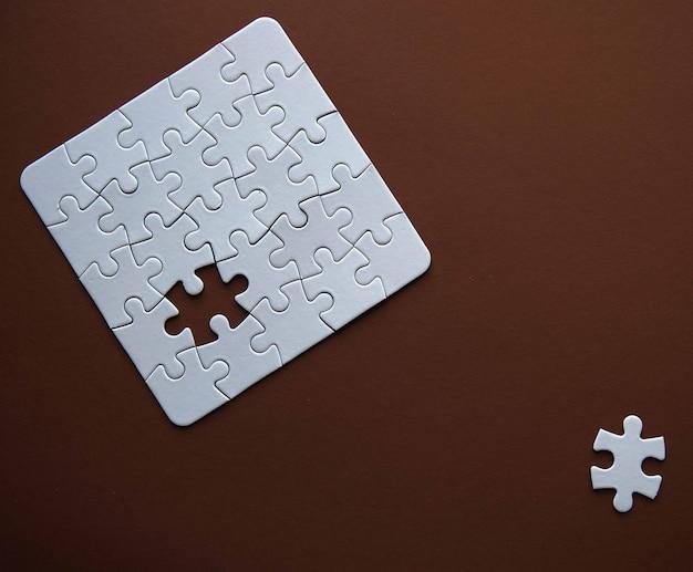 Weiße details des puzzlespiels auf braun