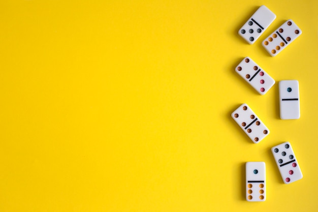 Weiße dominosteine auf gelbem hintergrund, draufsicht. brettspiel. platz für text
