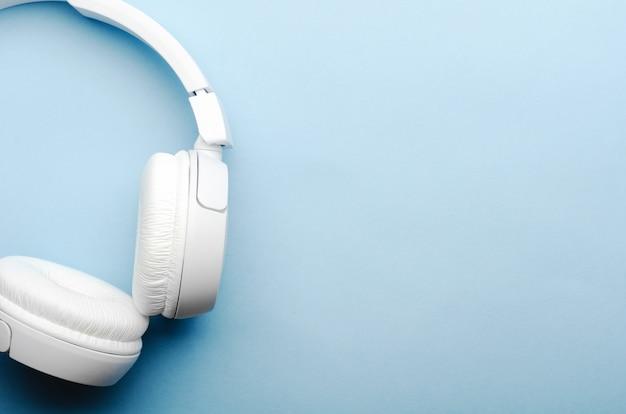 Weiße drahtlose bluetooth-kopfhörer über kopf auf blauem hintergrund. nahaufnahme, kopierraum, draufsicht, flatlay.