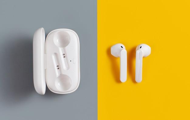 Weiße drahtlose kopfhörer auf gelber und grauer hintergrundoberansicht