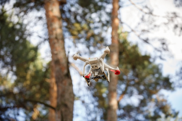 Weiße drohne, die im wald schwebt. uav drohnen-hubschrauber fliegt mit digitalkamera. lieferung der zukunft