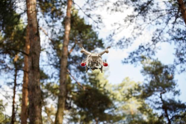 Weiße drohne, die im wald schwebt. uav drohnen-hubschrauber fliegt mit digitalkamera.
