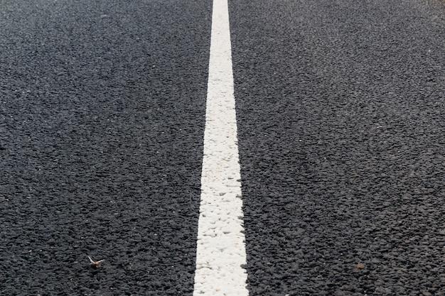 Weiße durchgezogene linie. straßenmarkierung auf einer asphaltstraße.